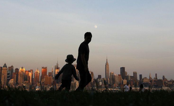 IlPost - 21 giugno 2013: un padre con sua figlia osservano lo skyline di New York mentre passeggiano in un parco di Weehawken, New Jersey (REUTERS/Gary Hershorn) - 21 giugno 2013: un padre con sua figlia osservano lo skyline di New York mentre passeggiano in un parco di Weehawken, New Jersey (REUTERS/Gary Hershorn)