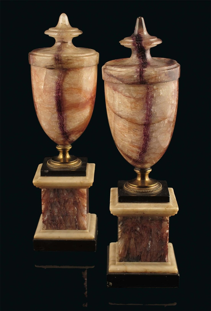 A pair of late George III blue john vases on stands, of semi-ovoid shape with integral covers having disc and pointed finials, on gilt brass socles to black and white marble square bases, 11in (28cm) h. (2)