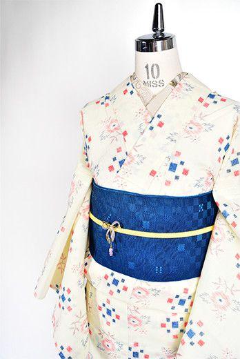 クリーム色の地に赤と青のトリコロールのようなカラーリングも愛らしく、花と市松風のスクエアパターンが染め出された化繊の夏着物です。