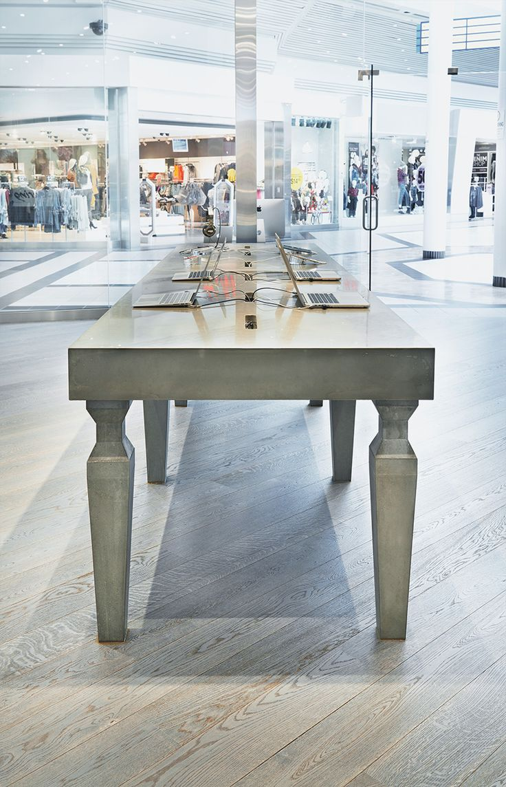 A custom made, concrete table in a store. Concrete displays can add a modern and industrial look to commercial retail settings, institutions, and events. #concrete #table #interior #design #modern #tabletop