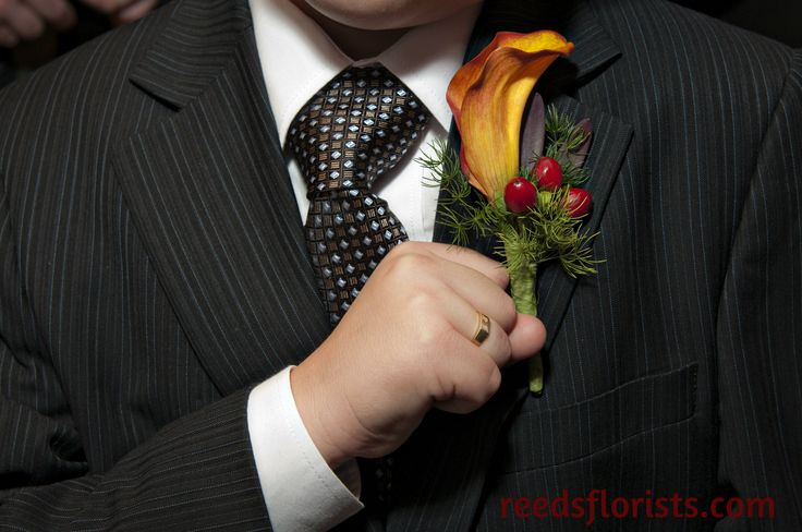 An excited junior groomsman shows off his calla lily boutonniere. Flowers by www.reedsflorists.com