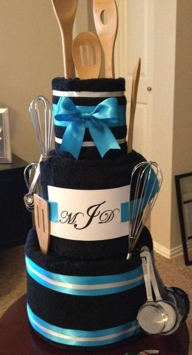 """a special """"shower cake""""  great gift idea  made with bath and hand towels and various kitchen items.  I recently made one of these cakes for a friend.  I learned that next time a make a towel cake I will buy cake plates to use for the bases (wilton from walmart or hobby lobby!) or I think that oven burner covers would work well too."""