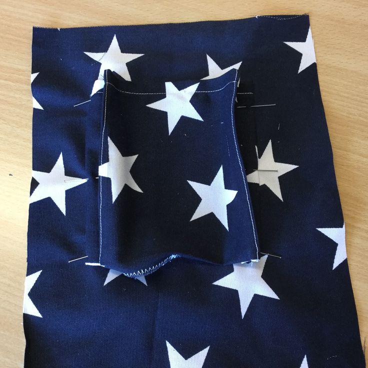 8. Nåla fast sidorna på fickan där den ska sitta med samma bredd som vecken. Sy fast dem med en stickning.