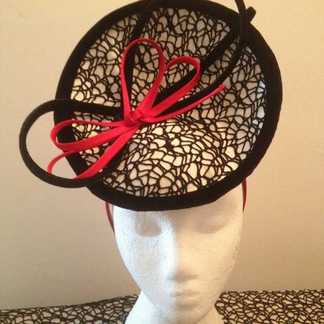 Dramatic monochrome headpiece with red bow