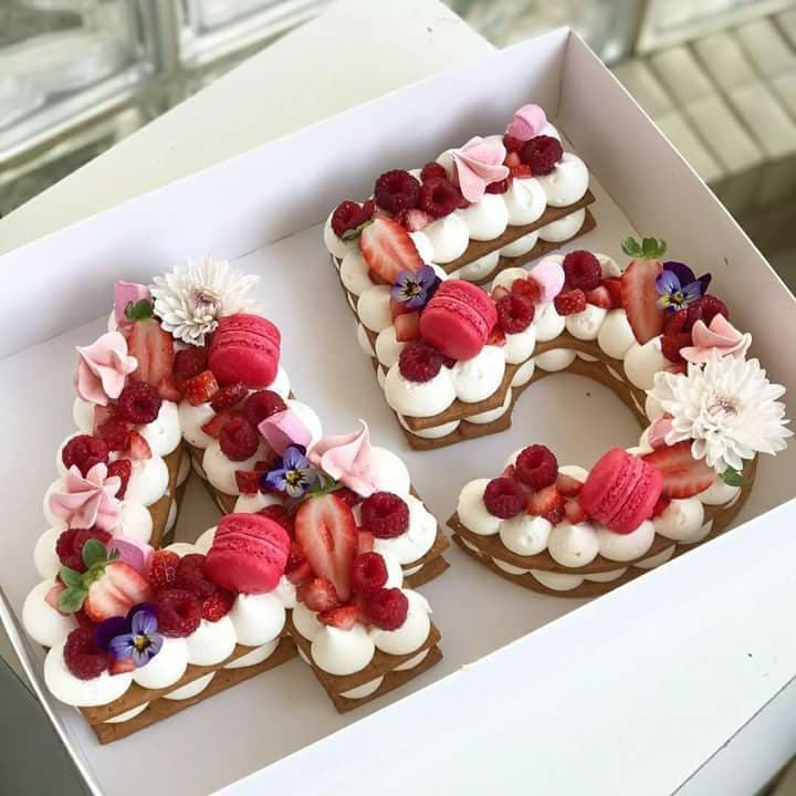 Pretty birthday cakes with fresh fruit macarons and flowers