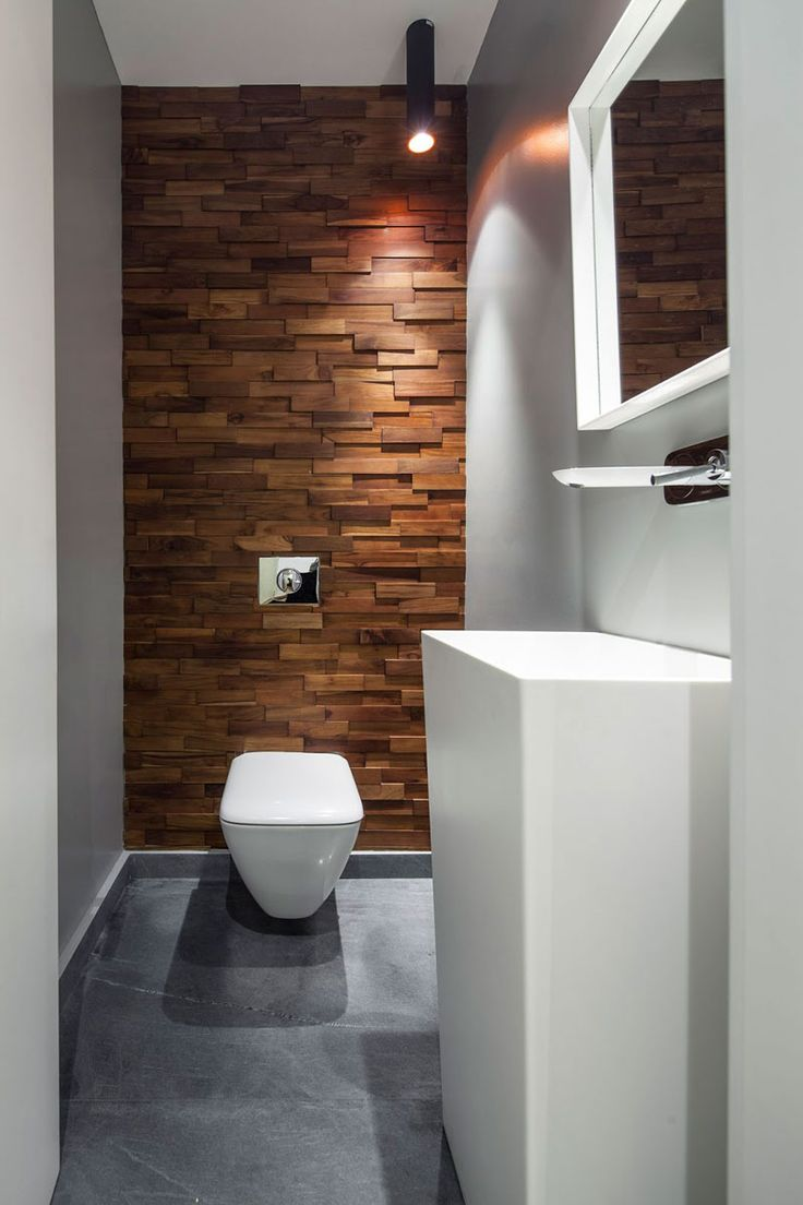 Accent Wall Ideas - 12 Different Ways To Cover Your Walls In Wood // Thin wood blocks running up this wall soften the industrial feel created by the concrete floor and warm up the white bathroom elements.
