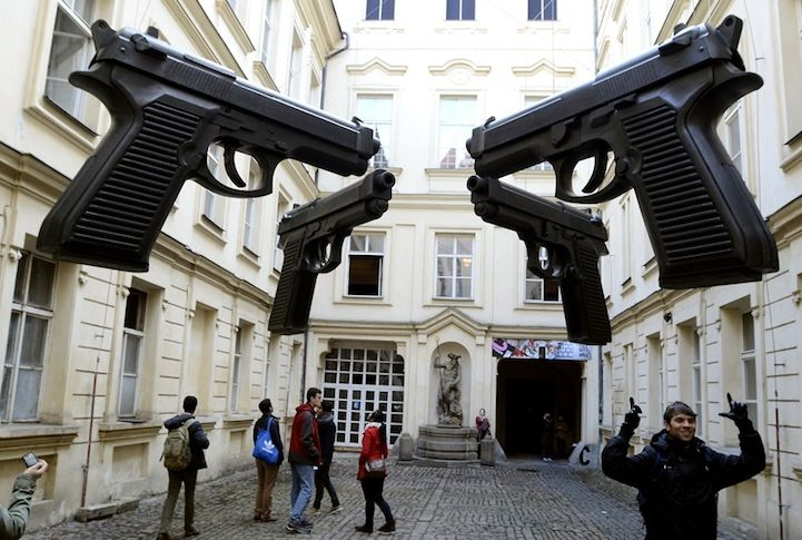"""Guns a Blazin' - My Modern Metropoli Czech artist David Černý is known for his controversial works. In fact, he was briefly arrested in 1991 for painting a Soviet tank pink, which served as a war memorial in central Prague. In this shot, visitors view his most recent artwork """"Guns"""" in the courtyard of the Artbanka Museum of Young Art in Prague."""