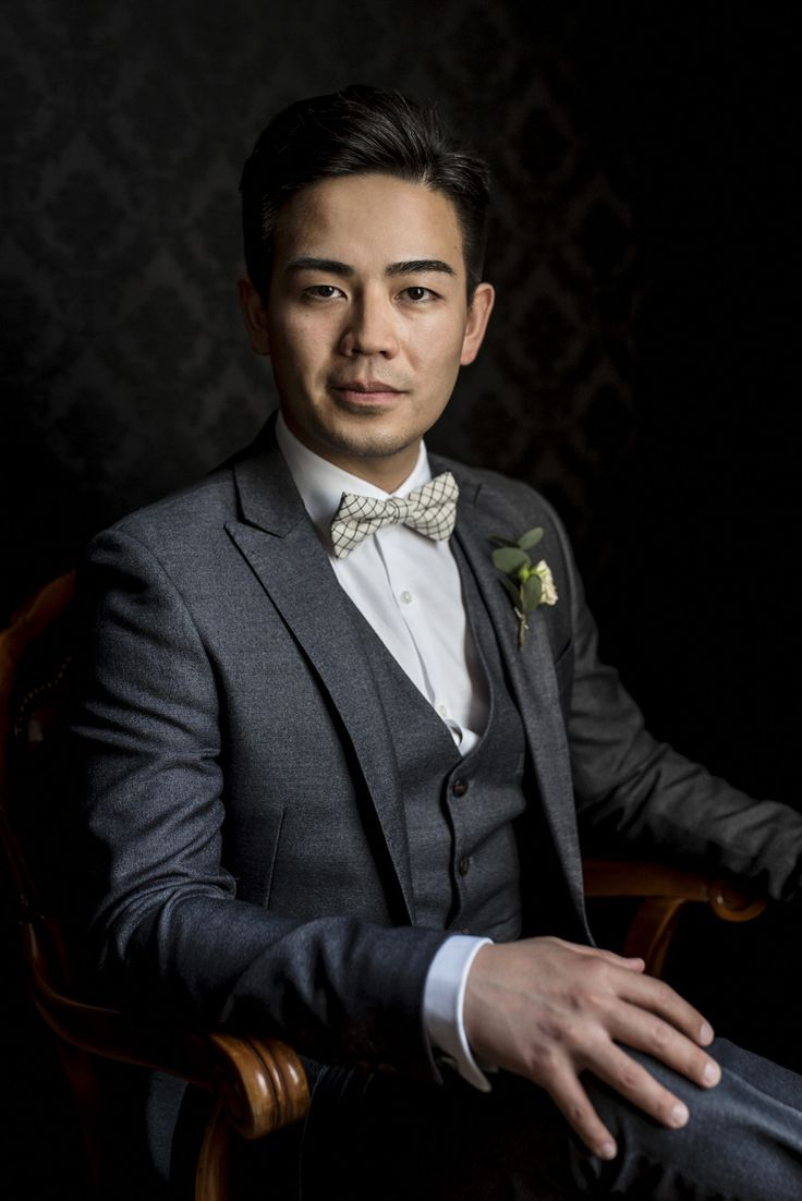Groom in grey suit and a white checkered bowtie,