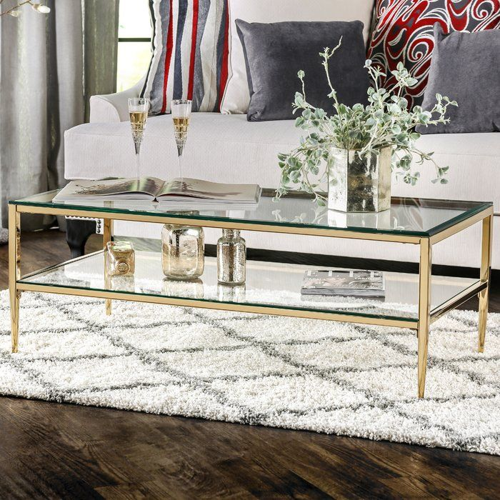 <p>Accent your home in chic elegance with the Travolta Open Shelf Coffee Table. Whether you're looking to complement a refined look or just add a touch of sophistication to a classically styled space, this charming coffee table is perfect for your space. Featuring a light silhouette, two tempered glass shelves, a sleek metallic finish, and slim tapered legs, this coffee table is a must-have for your home. </p><p>Try adding it to your living room beside your favorite...