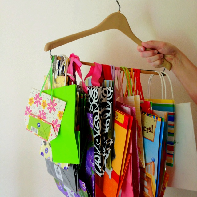 Gift bag storage! Shelf and floor space runs out quickly, but a men's pants hanger provides even more room for storage and for easy viewing of what you have available!