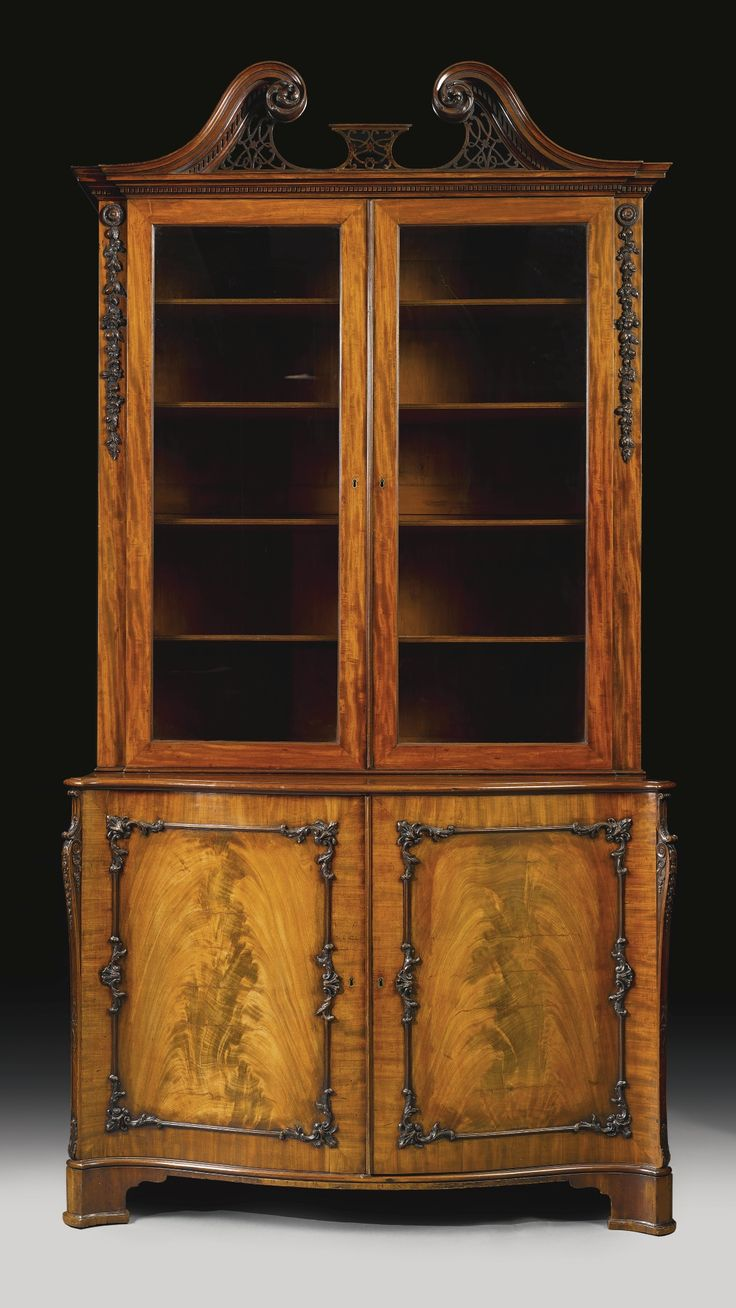 A fine George III mahogany bookcase cabinet, in the manner of Thomas Chippendale circa 1765 the lower section fitted with a pair of cupboard doors opening to a single sliding shelf; bearing a Stair & Company paper label. Sotheby's