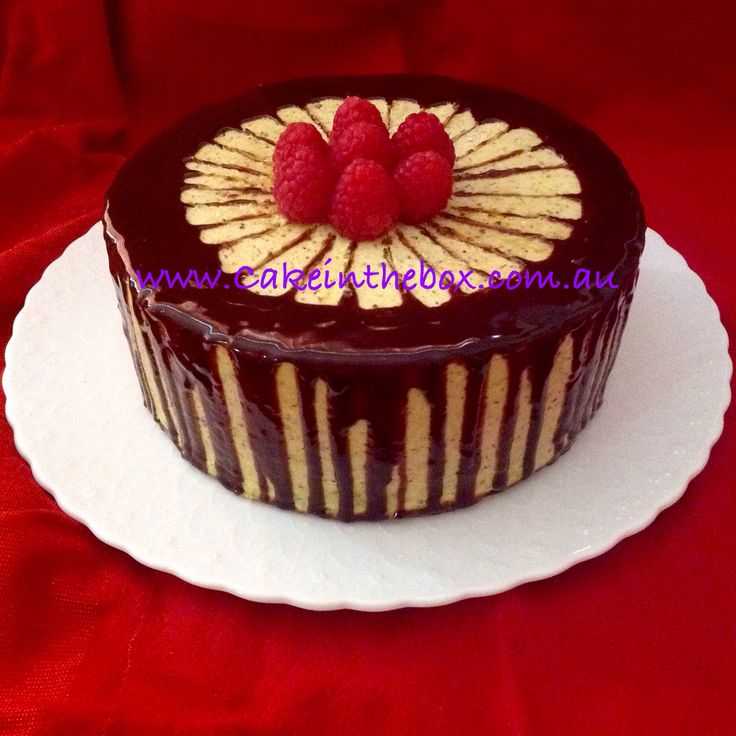 Gluten free chocolate cake with pistachio butter cream, chocolate ganache dripping and garnished with raspberries