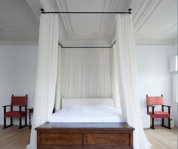 A modern day canopy channels its ancestors in a renovated 16th century structure. The bed curtains are attached to the ceiling via standard window drapery rods. Photo © Tim Van de Velde