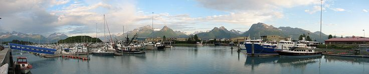 The port of Valdez, set against a natural backdrop of mountains under the midnight sun in July. Also visible is the shipping terminal for the Trans-Alaska Pipeline.