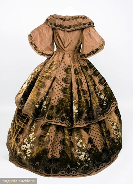 PRINTED & VOIDED VELVET EVENING GOWN, 1850s. Chocolate brown silk faille with border design of brown and cream roses, scrolls and columns in cut, uncut and voided velvet printed in shades of brown and cream, wide scoop neckline with attached collar, boned fitted bodice with rounded center front point, full short pagoda sleeves, full skirt in two tiers, back brass hook & eye closure, glazed linen bodice lining.                                      Price Realized:  $13,800.00