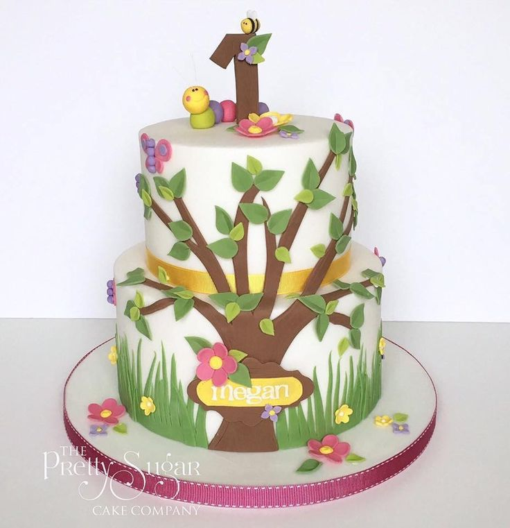 Bright colours first birthday cake with tree, blossoms and cute bugs detail