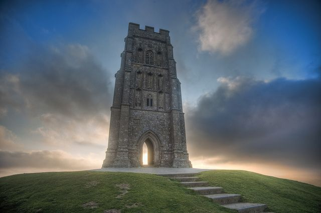 St. Michael's Tor in Glastonbury atop a hill. This is a very special and sacred site! I hope to return to one day.   Glastonbury Tor is a conical hill in Somerset, England, which is topped by a 14th-century St. Michael's Tower. Rich in legend it is a popular destination for visiting tourists, Grail theorists, ley-line enthusiasts, and those who make the climb to enjoy its sweeping view of Somerset countryside.