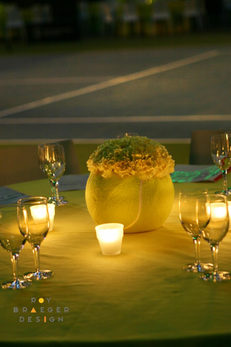 "Tennis Theme Centerpiece. A hollowed out 10"" tennis ball receives bright yellow carnations."