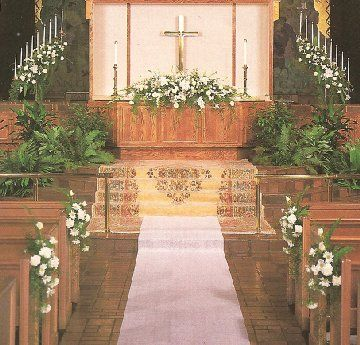 church decor idea with area rug and altar table at center stage-flowers, unity candle, marriage license