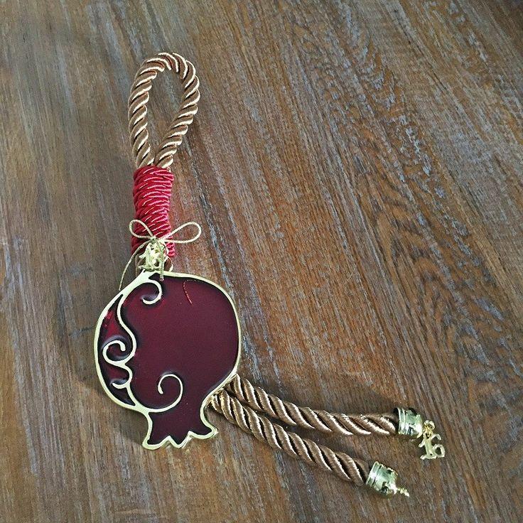 Μπρούτζινο ρόδι με κόκκινο σμάλτο και μπρούτζινο περίγραμμα, δεμένο με κόκκινο και χρυσό κορδόνι.