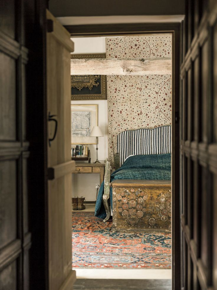 In the master bedroom of Docker Nook, a Queen Anne fabric panel hangs behind a headboard covered in an antique French linen; the chest at the end of the bed is an 18th-century Scandinavian blanket box and the rug is a 17th-century Oushak.