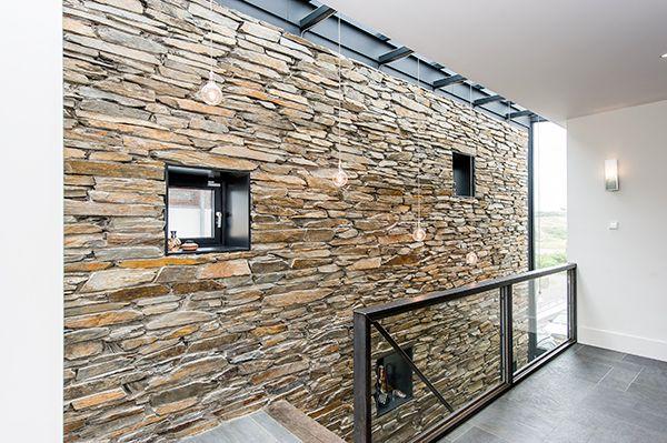 [ WOODWALL ]   Hal met een wand van Moellons, stenen afkomstig uit de Franse Alpen. Het hout van de trap refereert naar de bomen in de alpen, de stenen refereren naar de bergen en de grijze en witte accenten naar de sneeuw.  Architect: Van Manen  #wood #stairs #wand #villa #modern #interiordesign #luxury #moellons #vanmanen