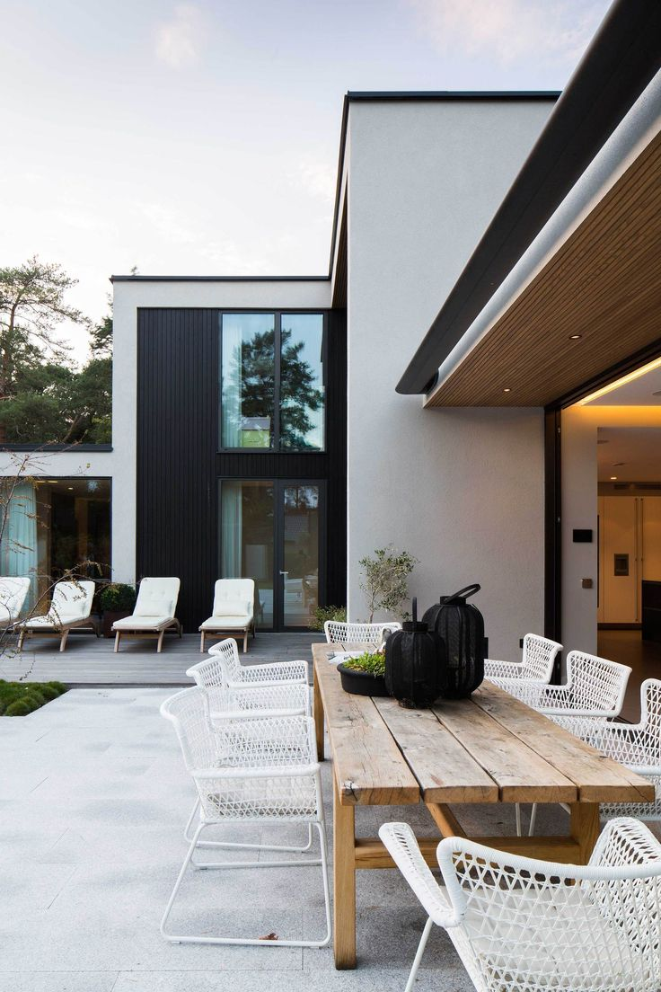 Contemporary patio with natural wood dining table woven white chairs. exterior with white stucco + black accents