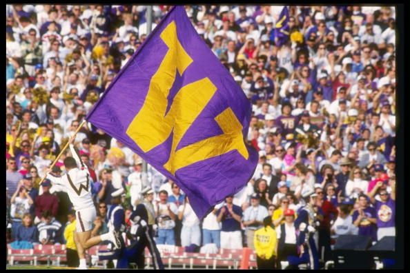 Univeristy of Washington Huskies cheerleader runs across the field with the school flag prior to start of the 1992 Rose Bowl against the University...