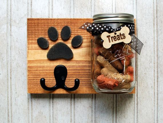 Dog leash holder and treat jar. Cute and practical, this treat/leash holder combination measures 8 x 6 long. All the wood is recycled or culled to create a functional piece of art. On the back are two heavy duty key hooks to assure proper hanging with bumpers to protect your wall. Each piece is hand cut and painted. The mason jar is attached with a hose clamp, and if need be can be loosened for cleaning.  This piece is sold as is, but custom orders are available, which can include, singl...