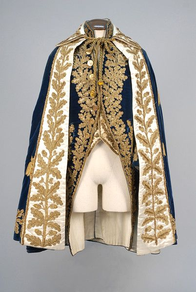 ca late 18th - early 19th century man's stunning court ensemble, including cobalt velvet coat with high stand collar, wide cuff and faux pockets, heavily decorated with foliate pattern metallic gold braid, cord, and sequins; plus a reproduction white satin waistcoat using trim from the original waistcoat; and lastly, a gorgeous deep blue velvet cape having white satin front borders with matching foliate decoration and the velvet appliqued with stylized gold owls. French