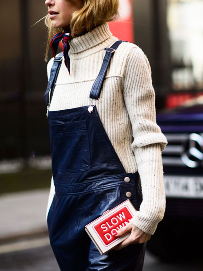 A red and navy silk scarf is tucked inside a beige turtleneck and worn with black leather overalls and a red and white clutch