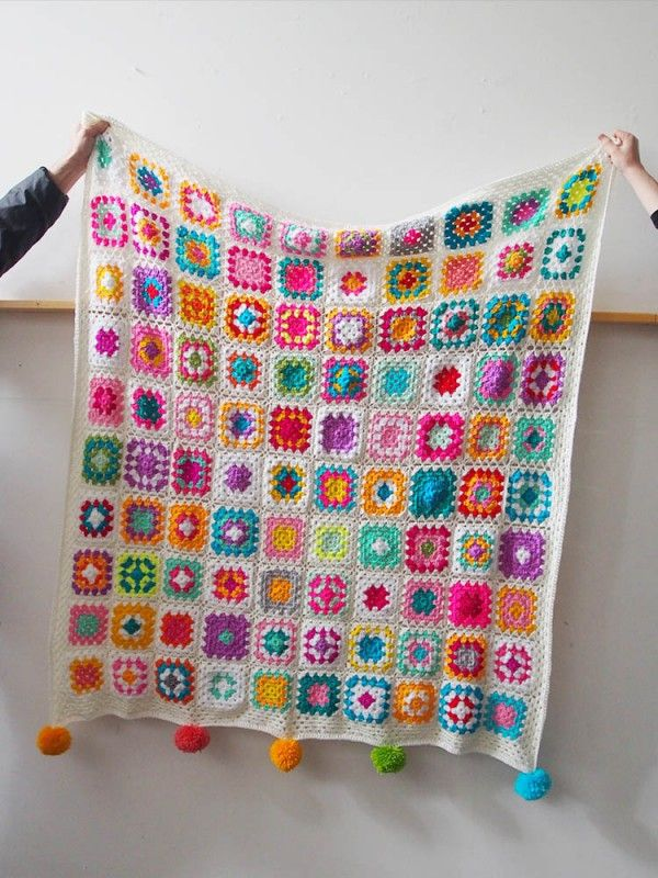 Crocheted Granny Square Blanket : I made a blanket for my friend! It's 100 granny squares, crocheted together with a nice, bright white background. And a pompom for each member of her family (including the dog!)