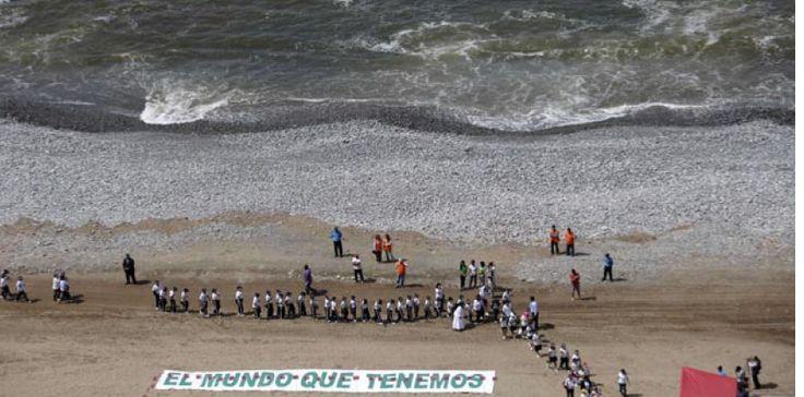 """Lima : ils se réunissent pour sauver la planète. Et la détruisent un peu plus.  Des enfants se réunissent pour former un arbre sur la plage. A côté une pancarte en espagnole : """"Le monde que nous voulons"""", le 4 décembre lors de la conférence de l'ONU sur le climat à Lima (Pérou).  Martin Mejia/AP/SIPA"""
