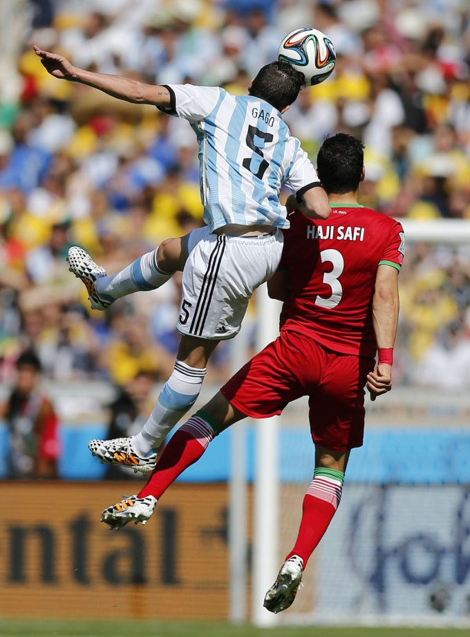 Argentina's Fernando Gago, left, challenges Iran's Ehsan Haji Safi during the group F World Cup soccer match between Argentina and Iran at t...