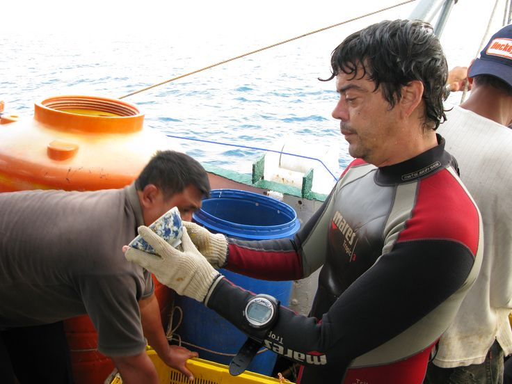 Alex Mirabal in Indonesia checking a Ming porcelain sample from an endangered wreck site