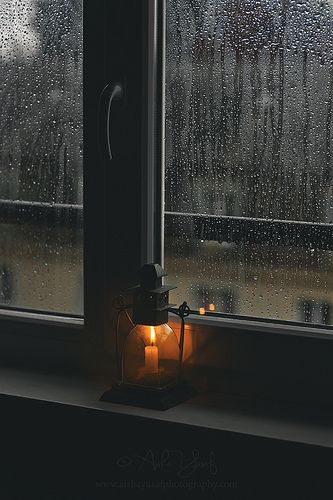 candle burning in a lantern + rain against the window