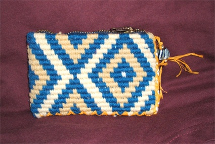 This is a detailed example of Taniko patterns,which is inspired by the idea of aramoana. The specific colours used are yellow,white and blue to create this purse.
