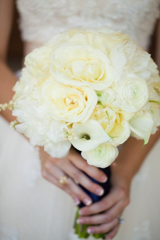 ivory ranunculus, lily of the valley, garden roses, mini calla lilies, and freesia.