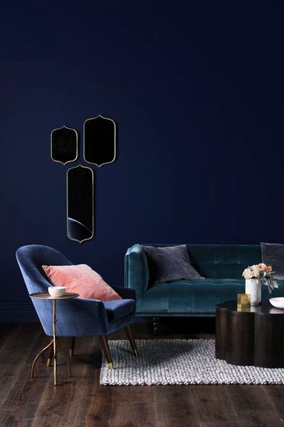 Living room with dark blue walls, a green velvet sofa, and a blue velvet armchair