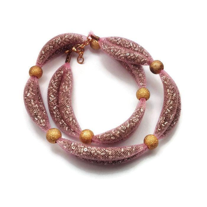 Collana in rete tubolare rosa riempita di conteria argentata, frammentata da perle a foro largo dorate per formare dei bei sorrisi
