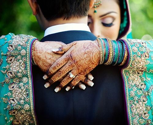 An Indian bride showing off her wedding jewelry while taking a moment to enjoy her groom