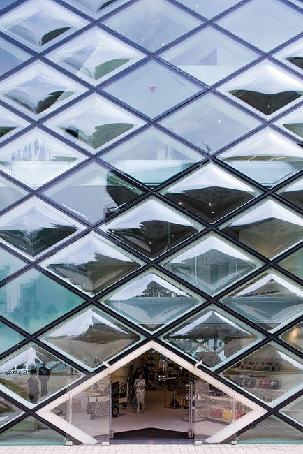 Prada shop, a glass and steel shopping experience made of diamond shaped windows, designed by Herzog & de Meuron in the fashionable Aoyama district in Tokyo, Japan