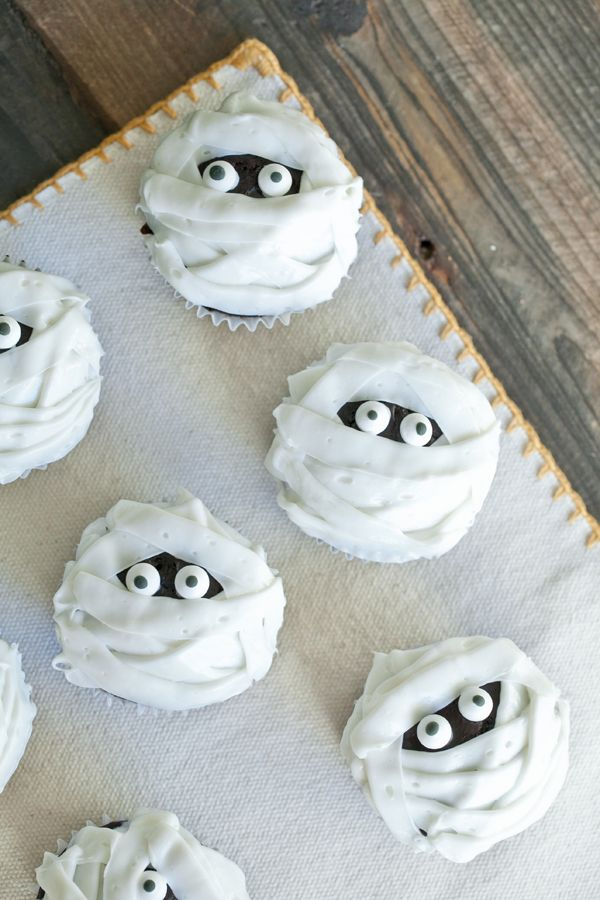 Dab a small amount of frosting on the back of the eyes, then stick them on the cupcake. Using a flat frosting tip, make lines across the cupcake, layering them and making different angles. It will start to resemble a mummy! Don't forget to leave those little eyes poking out : )