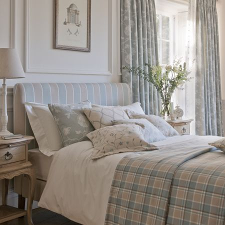 Clarke and Clarke - Ribble Valley Fabric Collection - Pale striped fabric headboard with matching checked bedding and patterned cushions, vintage side tables, floral curtains and a cream lamp