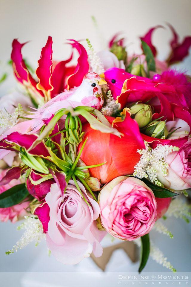 Bruidsboeket in roze en fuchsia kleuren: roze rozen, roze pioenrozen, fuchsia gloriosa lelie, afgewerkt met twee roze stoffen en veren vogeltjes.