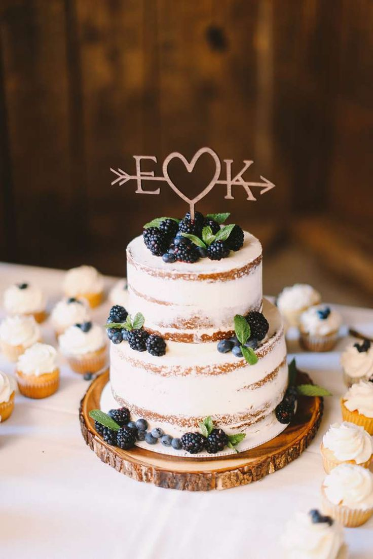 Wedding Cakes Worth Celebrating info@warrenwoodmanor.com Two-tier naked layered wedding cake with laser cut topper and berries
