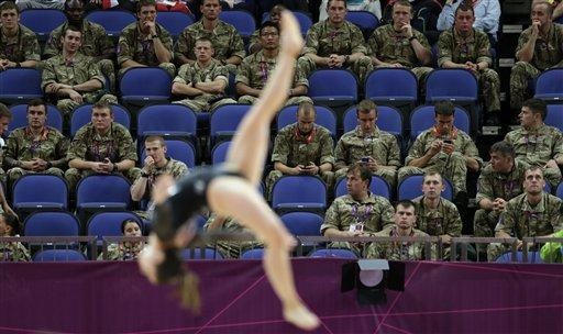 British soldiers watch gymnast Simona Castro Lazo from Chile perform during the Artistic Gymnastics women's qualification at the 2012 Summer Olympics, Sunday, July 29, 2012, in London. Troops, teachers and students are getting free tickets to fill prime seats that were empty at some Olympic venues on the first full day of competition. (AP Photo/Gregory Bull)