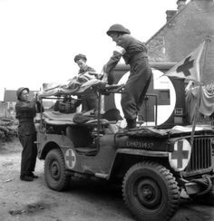 Privates L.E McKeating, A.E. Buell (in beret) and L.F. McCadam help take a stretcher case from the jeep ambulance. To the right is an ambulance carrying a white 76 on a black background identifying a vehicle of the 22nd Field Ambulance Company, 8th Infantry Brigade.