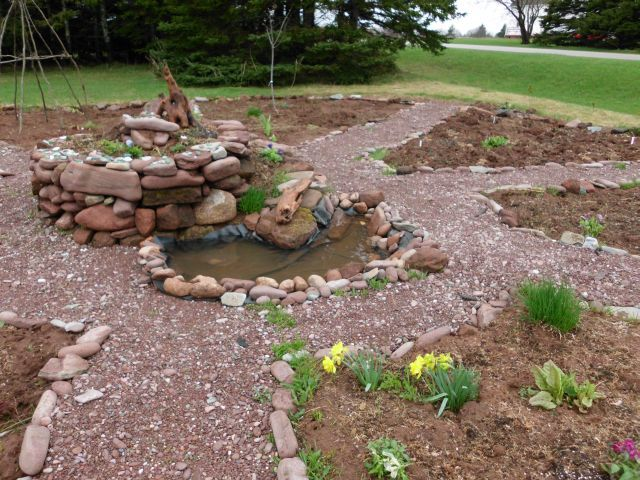 mandala garden with herb spiral pond at base at the
