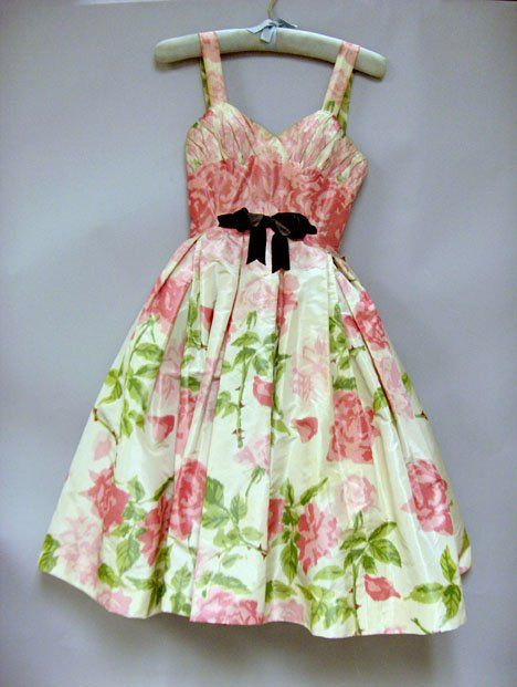 "Pierre Balmain Haute Couture 1950s   party dress. Fitted bodice with shoulder straps, vertically shirred and gathered bust. Waist constructed from patches of fabric to isolate the brighter pink of the motif, black velvet bow at the center, full skirt springing from the waistline in a pink and green rose"" print on cream silk crepe de chine. Supported by several layers of acetate and tulle crinolines, the bodice fully structured with light boning and shaped with lingerie-style wiring and…"